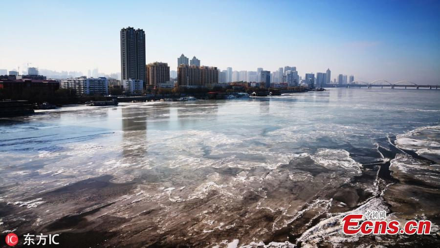 A winter swimming enthusiast broke the ice and jumped into the Songhua River to start his winter swimming season in Harbin, Northeast China\'s Heilongjiang province, on Nov 23, 2018. Hundreds of winter swimming enthusiasts swim in the river every year. (Photo/VCG)