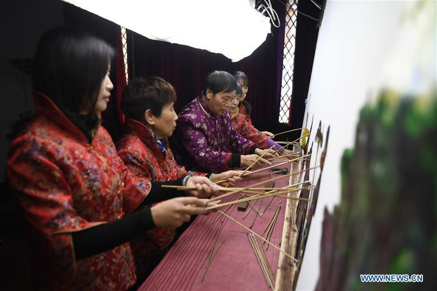 Zhang Kunrong(C) performs with his apprentices in a shadow puppetry show in Haining City, east China\'s Zhejiang Province, Nov. 20, 2018. Zhang Kunrong, 79, a locally born shadow puppetry player, is an inheritor of the Haining shadow puppetry, a form of traditional theatre acted by colorful silhouette figures made from leather or paper, accompanied by music and singing. A typical variety popular in south China, Haining shadow puppetry, a national intangible cultural heritage, has a history of about 900 years dating back to the Southern Song Dynasty (AD 1127-1279). Obsessed with the shadow play since childhood, Zhang Kunrong was recruited to the provincial shadow puppetry troupe in 1958 and soon became a mainstay after two year\'s practice and in the later years staged performances at home and abroad as Haining shadow puppetry grows popular. Nowadays, Zhang works more on script writing, directing and teaching apprentices. Haining shadow puppetry was listed as one of the state-level intangible cultural heritages in 2006 and was included in the UNESCO Intangible Cultural Heritage of Humanity list in 2011. (Xinhua/Huang Zongzhi)