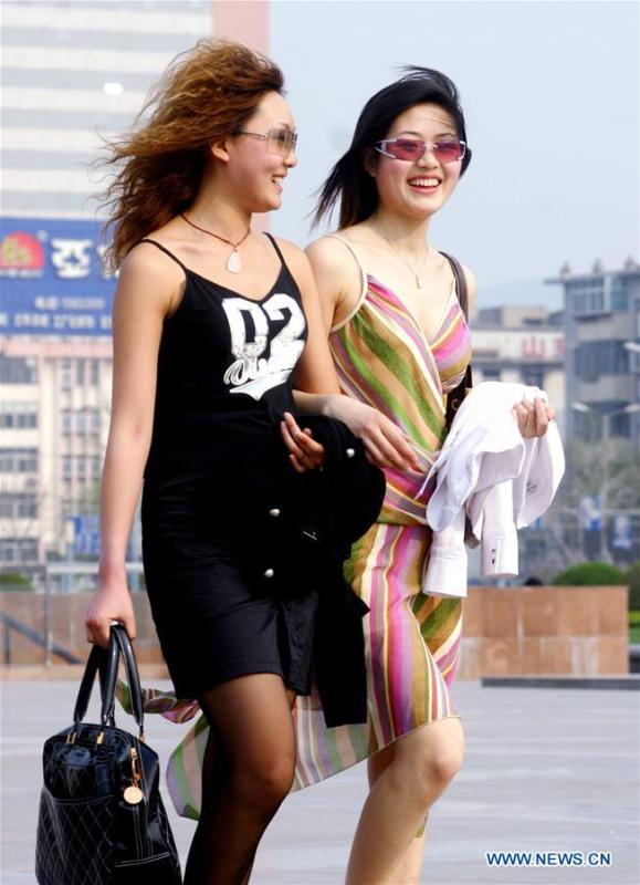 File photo taken on April 5, 2005 shows two young ladies walking across the Quancheng square in Jinan, east China\'s Shandong Province. From 1978 when China started its reform and opening-up policy, a door to the outside world has been opened. Along with the imported commodities, fashion ideas inevitably slipped into China and since then the country, which was somewhat lack of fashion diversity, started its journey to pursue fashions. Over the past four decades, the thirst for beauty has driven Chinese people to pursue every possible fashionable element. The change first came with dress when colorful and diversified clothing prevailed as against the former dominant blue and grey. For a time, men and women raced to hairdressers\' just for trendy hairdos. Eating McDonald\'s or western cuisine even once was regarded as a fashionable thing. However, the most conspicuous change is that Chinese people have become more inclusive and they tend to accept new fashions, styles and concepts. China nowadays is dazzling the world not only on the fashion stage but in many other fields. Changes in fashions, as a profile of society, has well interpreted the benefits to people brought by China\'s reform and opening-up policy. (Xinhua)