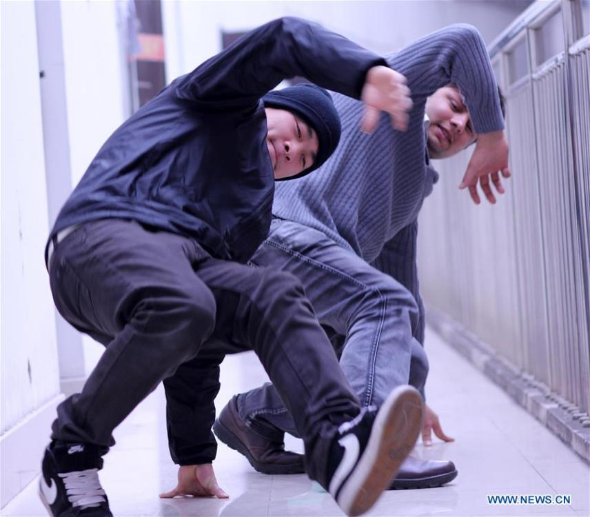 File photo taken on March 11, 2011 shows Abdul Mubeen (back) practicing dance with Wang Yang, a member of the hip-hop team \
