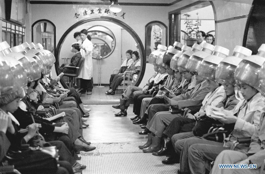 File photo taken in 1982 shows people getting their hair permed at a barber shop in east China\'s Shanghai. From 1978 when China started its reform and opening-up policy, a door to the outside world has been opened. Along with the imported commodities, fashion ideas inevitably slipped into China and since then the country, which was somewhat lack of fashion diversity, started its journey to pursue fashions. Over the past four decades, the thirst for beauty has driven Chinese people to pursue every possible fashionable element. The change first came with dress when colorful and diversified clothing prevailed as against the former dominant blue and grey. For a time, men and women raced to hairdressers\' just for trendy hairdos. Eating McDonald\'s or western cuisine even once was regarded as a fashionable thing. However, the most conspicuous change is that Chinese people have become more inclusive and they tend to accept new fashions, styles and concepts. China nowadays is dazzling the world not only on the fashion stage but in many other fields. Changes in fashions, as a profile of society, has well interpreted the benefits to people brought by China\'s reform and opening-up policy. (Xinhua)