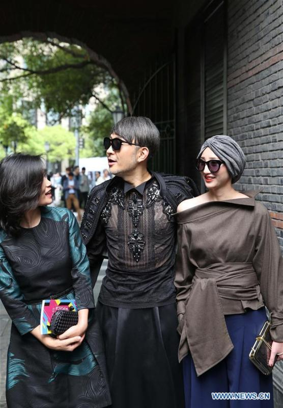 File photo taken on April 11, 2016 shows people wearing fashionable costumes outside the venue of a fashion show in east China\'s Shanghai. From 1978 when China started its reform and opening-up policy, a door to the outside world has been opened. Along with the imported commodities, fashion ideas inevitably slipped into China and since then the country, which was somewhat lack of fashion diversity, started its journey to pursue fashions. Over the past four decades, the thirst for beauty has driven Chinese people to pursue every possible fashionable element. The change first came with dress when colorful and diversified clothing prevailed as against the former dominant blue and grey. For a time, men and women raced to hairdressers\' just for trendy hairdos. Eating McDonald\'s or western cuisine even once was regarded as a fashionable thing. However, the most conspicuous change is that Chinese people have become more inclusive and they tend to accept new fashions, styles and concepts. China nowadays is dazzling the world not only on the fashion stage but in many other fields. Changes in fashions, as a profile of society, has well interpreted the benefits to people brought by China\'s reform and opening-up policy. (Xinhua/Ren Long)