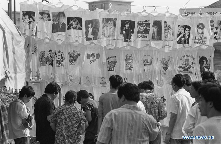 File photo issued on July 20, 1992 shows people selecting T-shirt printed with portraits of pop actors and singers in Beijing, capital of China. From 1978 when China started its reform and opening-up policy, a door to the outside world has been opened. Along with the imported commodities, fashion ideas inevitably slipped into China and since then the country, which was somewhat lack of fashion diversity, started its journey to pursue fashions. Over the past four decades, the thirst for beauty has driven Chinese people to pursue every possible fashionable element. The change first came with dress when colorful and diversified clothing prevailed as against the former dominant blue and grey. For a time, men and women raced to hairdressers\' just for trendy hairdos. Eating McDonald\'s or western cuisine even once was regarded as a fashionable thing. However, the most conspicuous change is that Chinese people have become more inclusive and they tend to accept new fashions, styles and concepts. China nowadays is dazzling the world not only on the fashion stage but in many other fields. Changes in fashions, as a profile of society, has well interpreted the benefits to people brought by China\'s reform and opening-up policy. (Xinhua/Zeng Huang)