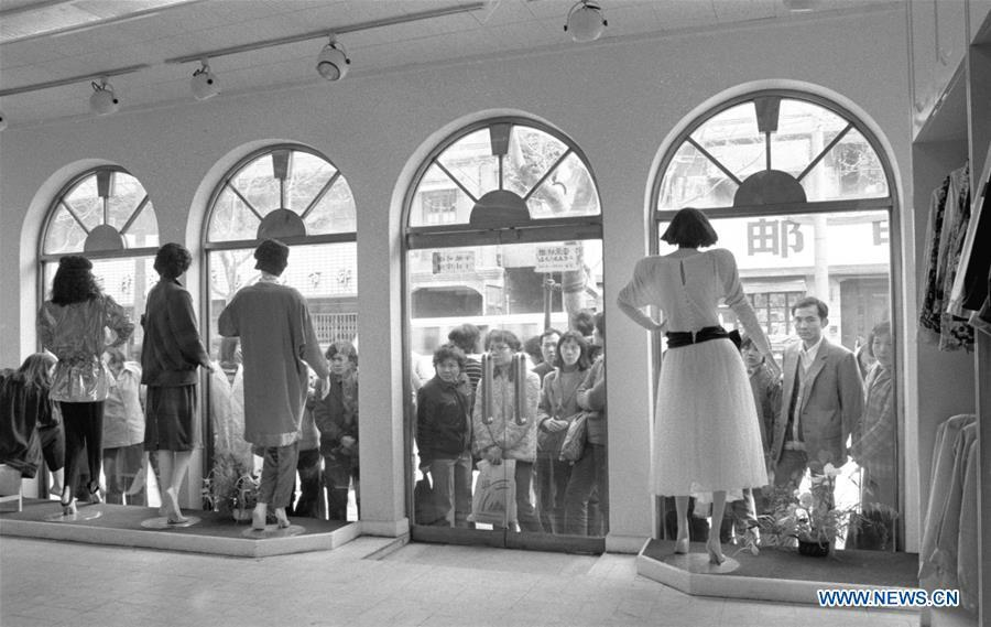 File photo issued on May 15, 1987 shows consumers waiting outside a clothing store of a fashion brand in east China\'s Shanghai. From 1978 when China started its reform and opening-up policy, a door to the outside world has been opened. Along with the imported commodities, fashion ideas inevitably slipped into China and since then the country, which was somewhat lack of fashion diversity, started its journey to pursue fashions. Over the past four decades, the thirst for beauty has driven Chinese people to pursue every possible fashionable element. The change first came with dress when colorful and diversified clothing prevailed as against the former dominant blue and grey. For a time, men and women raced to hairdressers\' just for trendy hairdos. Eating McDonald\'s or western cuisine even once was regarded as a fashionable thing. However, the most conspicuous change is that Chinese people have become more inclusive and they tend to accept new fashions, styles and concepts. China nowadays is dazzling the world not only on the fashion stage but in many other fields. Changes in fashions, as a profile of society, has well interpreted the benefits to people brought by China\'s reform and opening-up policy. (Xinhua/Xu Yigen)