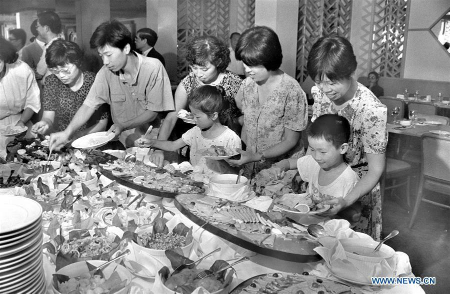 File photo taken in 1990 shows people selecting western food at a restaurant in Suzhou, east China\'s Jiangsu Province. From 1978 when China started its reform and opening-up policy, a door to the outside world has been opened. Along with the imported commodities, fashion ideas inevitably slipped into China and since then the country, which was somewhat lack of fashion diversity, started its journey to pursue fashions. Over the past four decades, the thirst for beauty has driven Chinese people to pursue every possible fashionable element. The change first came with dress when colorful and diversified clothing prevailed as against the former dominant blue and grey. For a time, men and women raced to hairdressers\' just for trendy hairdos. Eating McDonald\'s or western cuisine even once was regarded as a fashionable thing. However, the most conspicuous change is that Chinese people have become more inclusive and they tend to accept new fashions, styles and concepts. China nowadays is dazzling the world not only on the fashion stage but in many other fields. Changes in fashions, as a profile of society, has well interpreted the benefits to people brought by China\'s reform and opening-up policy. (Xinhua/Fang Ailing)