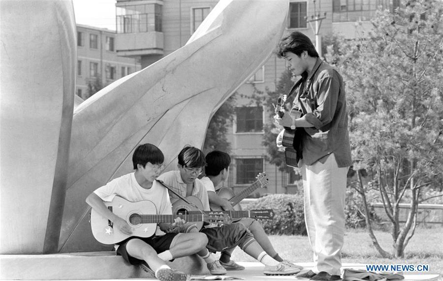 File photo issued on Aug. 24, 1992 shows middle school students singing during a rehearsal at a park in Beijing, capital of China. From 1978 when China started its reform and opening-up policy, a door to the outside world has been opened. Along with the imported commodities, fashion ideas inevitably slipped into China and since then the country, which was somewhat lack of fashion diversity, started its journey to pursue fashions. Over the past four decades, the thirst for beauty has driven Chinese people to pursue every possible fashionable element. The change first came with dress when colorful and diversified clothing prevailed as against the former dominant blue and grey. For a time, men and women raced to hairdressers\' just for trendy hairdos. Eating McDonald\'s or western cuisine even once was regarded as a fashionable thing. However, the most conspicuous change is that Chinese people have become more inclusive and they tend to accept new fashions, styles and concepts. China nowadays is dazzling the world not only on the fashion stage but in many other fields. Changes in fashions, as a profile of society, has well interpreted the benefits to people brought by China\'s reform and opening-up policy. (Xinhua/Zeng Huang)
