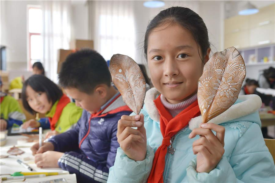 A student shows her leaf art at a primary school in Qingdao, East China\'s Shandong Province, on Nov. 19, 2018. (Photo/Asianewsphoto)