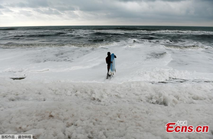 An Indian fisherman pulls in his fishing net as foamy discharge, caused by pollutants, mix with surf at a beach in Chennai on November 22, 2018.  High levels of sewage and industrial waste was claimed to be the cause of the foam, officials said. (Photo/Agencies)