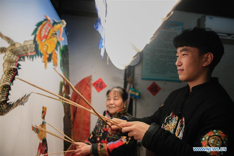 Liu Fan(R), one of Zhang Kunrong\'s apprentices, performs in a shadow puppetry show in Haining City, east China\'s Zhejiang Province, Nov. 21, 2018. Zhang Kunrong, 79, a locally born shadow puppetry player, is an inheritor of the Haining shadow puppetry, a form of traditional theatre acted by colorful silhouette figures made from leather or paper, accompanied by music and singing. A typical variety popular in south China, Haining shadow puppetry, a national intangible cultural heritage, has a history of about 900 years dating back to the Southern Song Dynasty (AD 1127-1279). Obsessed with the shadow play since childhood, Zhang Kunrong was recruited to the provincial shadow puppetry troupe in 1958 and soon became a mainstay after two year\'s practice and in the later years staged performances at home and abroad as Haining shadow puppetry grows popular. Nowadays, Zhang works more on script writing, directing and teaching apprentices. Haining shadow puppetry was listed as one of the state-level intangible cultural heritages in 2006 and was included in the UNESCO Intangible Cultural Heritage of Humanity list in 2011. (Xinhua/Zhu Weixi)