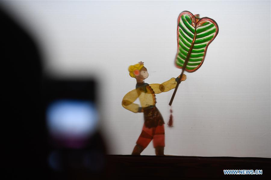 A spectator takes a photo during a shadow puppetry show in Haining City, east China\'s Zhejiang Province, Nov. 21, 2018. Zhang Kunrong, 79, a locally born shadow puppetry player, is an inheritor of the Haining shadow puppetry, a form of traditional theatre acted by colorful silhouette figures made from leather or paper, accompanied by music and singing. A typical variety popular in south China, Haining shadow puppetry, a national intangible cultural heritage, has a history of about 900 years dating back to the Southern Song Dynasty (AD 1127-1279). Obsessed with the shadow play since childhood, Zhang Kunrong was recruited to the provincial shadow puppetry troupe in 1958 and soon became a mainstay after two year\'s practice and in the later years staged performances at home and abroad as Haining shadow puppetry grows popular. Nowadays, Zhang works more on script writing, directing and teaching apprentices. Haining shadow puppetry was listed as one of the state-level intangible cultural heritages in 2006 and was included in the UNESCO Intangible Cultural Heritage of Humanity list in 2011. (Xinhua/Huang Zongzhi)