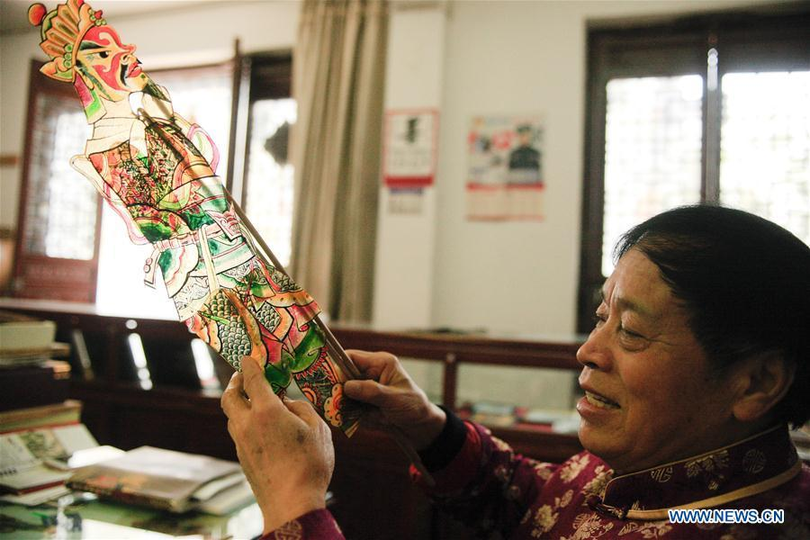Zhang Kunrong sews parts together to make a shadow puppetry piece in Haining City, east China\'s Zhejiang Province, Nov. 20, 2018. Zhang Kunrong, 79, a locally born shadow puppetry player, is an inheritor of the Haining shadow puppetry, a form of traditional theatre acted by colorful silhouette figures made from leather or paper, accompanied by music and singing. A typical variety popular in south China, Haining shadow puppetry, a national intangible cultural heritage, has a history of about 900 years dating back to the Southern Song Dynasty (AD 1127-1279). Obsessed with the shadow play since childhood, Zhang Kunrong was recruited to the provincial shadow puppetry troupe in 1958 and soon became a mainstay after two year\'s practice and in the later years staged performances at home and abroad as Haining shadow puppetry grows popular. Nowadays, Zhang works more on script writing, directing and teaching apprentices. Haining shadow puppetry was listed as one of the state-level intangible cultural heritages in 2006 and was included in the UNESCO Intangible Cultural Heritage of Humanity list in 2011. (Xinhua/Zhu Weixi)