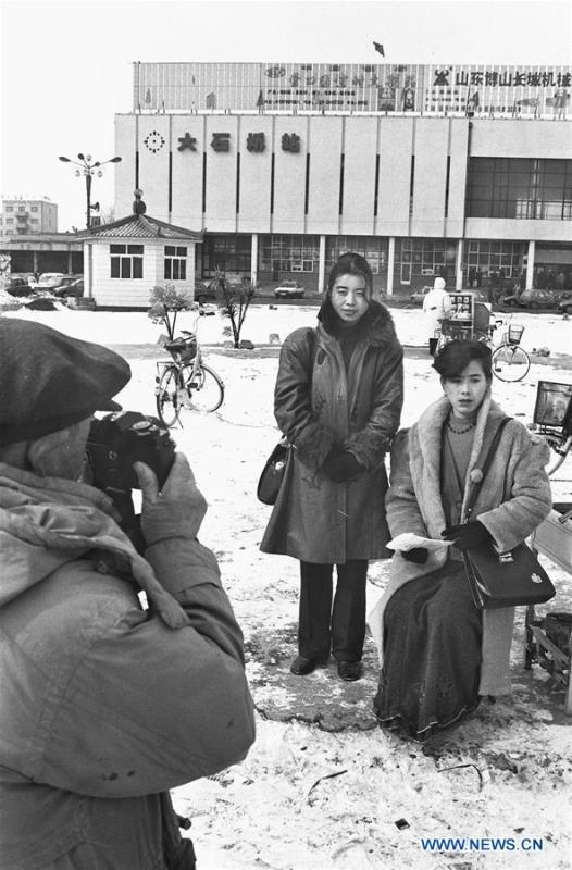 File photo issued on Feb. 24, 1997 shows residents in fashionable costumes posing for photo at a railway station in Dashiqiao, northeast China\'s Liaoning Province. From 1978 when China started its reform and opening-up policy, a door to the outside world has been opened. Along with the imported commodities, fashion ideas inevitably slipped into China and since then the country, which was somewhat lack of fashion diversity, started its journey to pursue fashions. Over the past four decades, the thirst for beauty has driven Chinese people to pursue every possible fashionable element. The change first came with dress when colorful and diversified clothing prevailed as against the former dominant blue and grey. For a time, men and women raced to hairdressers\' just for trendy hairdos. Eating McDonald\'s or western cuisine even once was regarded as a fashionable thing. However, the most conspicuous change is that Chinese people have become more inclusive and they tend to accept new fashions, styles and concepts. China nowadays is dazzling the world not only on the fashion stage but in many other fields. Changes in fashions, as a profile of society, has well interpreted the benefits to people brought by China\'s reform and opening-up policy. (Xinhua/Li Yonghong)