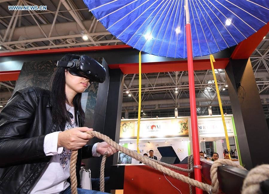 A visitor tries a virtual reality headset in the 8th Chinese Museums and Relevant Products and Technologies Exposition (MPT-Expo) in Fuzhou, capital of southeast China\'s Fujian Province, Nov. 23, 2018. (Xinhua/Li He)
