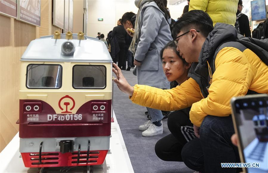Visitors look at the model of locomotive during a major exhibition to commemorate the 40th anniversary of China\'s reform and opening-up at the National Museum of China in Beijing, capital of China, Nov. 24, 2018. (Xinhua/Yin Gang)