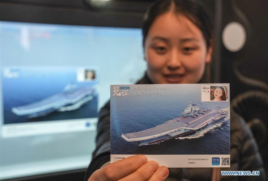 A visitor displays a customized postcard at the exhibition area of Xinhua News Agency during a major exhibition to commemorate the 40th anniversary of China\'s reform and opening-up at the National Museum of China in Beijing, capital of China, Nov. 24, 2018. (Xinhua/Yin Gang)