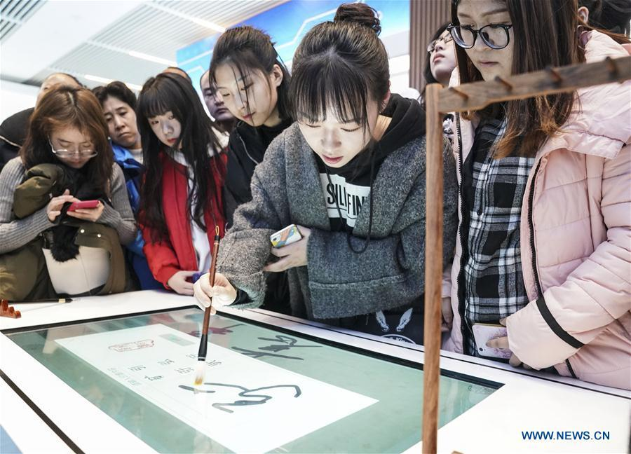 Visitors experience intelligent calligraphy writing desk during a major exhibition to commemorate the 40th anniversary of China\'s reform and opening-up at the National Museum of China in Beijing, capital of China, Nov. 24, 2018. (Xinhua/Yin Gang)