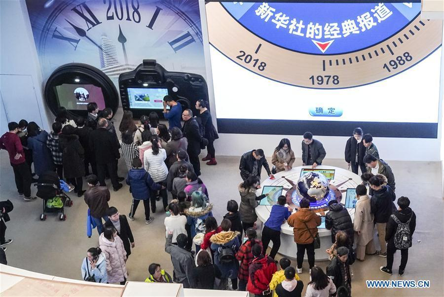 Visitors experience customized postcard making at the exhibition area of Xinhua News Agency during a major exhibition to commemorate the 40th anniversary of China\'s reform and opening-up at the National Museum of China in Beijing, capital of China, Nov. 24, 2018. (Xinhua/Yin Gang)