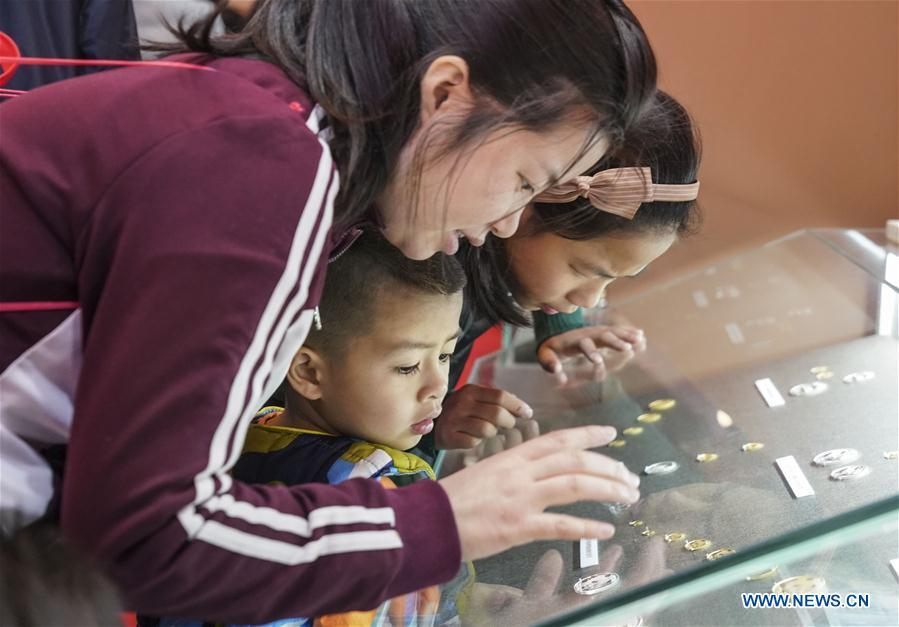 Visitors look at the commemorative coins during a major exhibition to commemorate the 40th anniversary of China\'s reform and opening-up at the National Museum of China in Beijing, capital of China, Nov. 24, 2018. (Xinhua/Yin Gang)