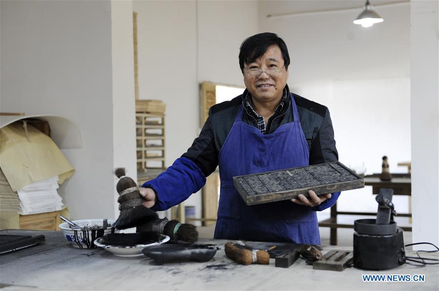 Lei Shitai presents his printing tools in Chanshan Village of Qinxi Town, Jingxian County, in east China\'s Anhui Province, Nov. 23, 2018. Lei, 52, born in neighboring Jiangxi Province, started his career as a typography printer when he finished his apprenticeship with his uncle who he followed since he was 17. The traditional printing method witnessed an increasingly hard time in the recent years as a livelihood. It was in 2017 when he decided to move to Chanshan at the invitation of Kai Yuanhong, a local cabinet maker, to cooperate in a broader way. Lei is now working with the traditional technique in a larger scale. (Xinhua/Xu Liang)