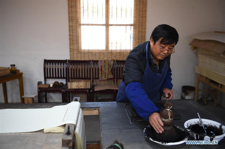 Lei Shitai works in Chanshan Village of Qinxi Town, Jingxian County, in east China\'s Anhui Province, Nov. 23, 2018. Lei, 52, born in neighboring Jiangxi Province, started his career as a typography printer when he finished his apprenticeship with his uncle who he followed since he was 17. The traditional printing method witnessed an increasingly hard time in the recent years as a livelihood. It was in 2017 when he decided to move to Chanshan at the invitation of Kai Yuanhong, a local cabinet maker, to cooperate in a broader way. Lei is now working with the traditional technique in a larger scale. (Xinhua/Zhang Duan)
