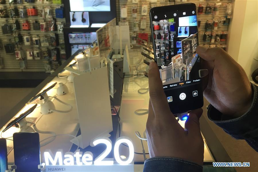 People tries a Huawei smart phone in a shopping mall in Barcelona, Spain, on Nov. 25, 2018. More and more Spanish consumers accept Chinese high-tech brands, which now can be seen in daily life across Spain. (Xinhua/Zheng Huansong)