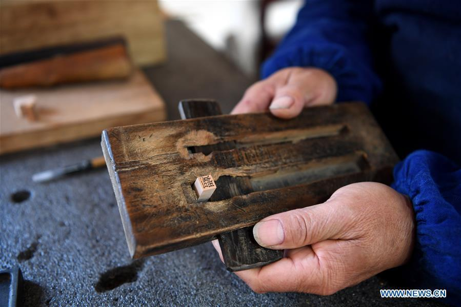 Lei Shitai presents his printing tools in Chanshan Village of Qinxi Town, Jingxian County, in east China\'s Anhui Province, Nov. 23, 2018. Lei, 52, born in neighboring Jiangxi Province, started his career as a typography printer when he finished his apprenticeship with his uncle who he followed since he was 17. The traditional printing method witnessed an increasingly hard time in the recent years as a livelihood. It was in 2017 when he decided to move to Chanshan at the invitation of Kai Yuanhong, a local cabinet maker, to cooperate in a broader way. Lei is now working with the traditional technique in a larger scale. (Xinhua/Liu Junxi)