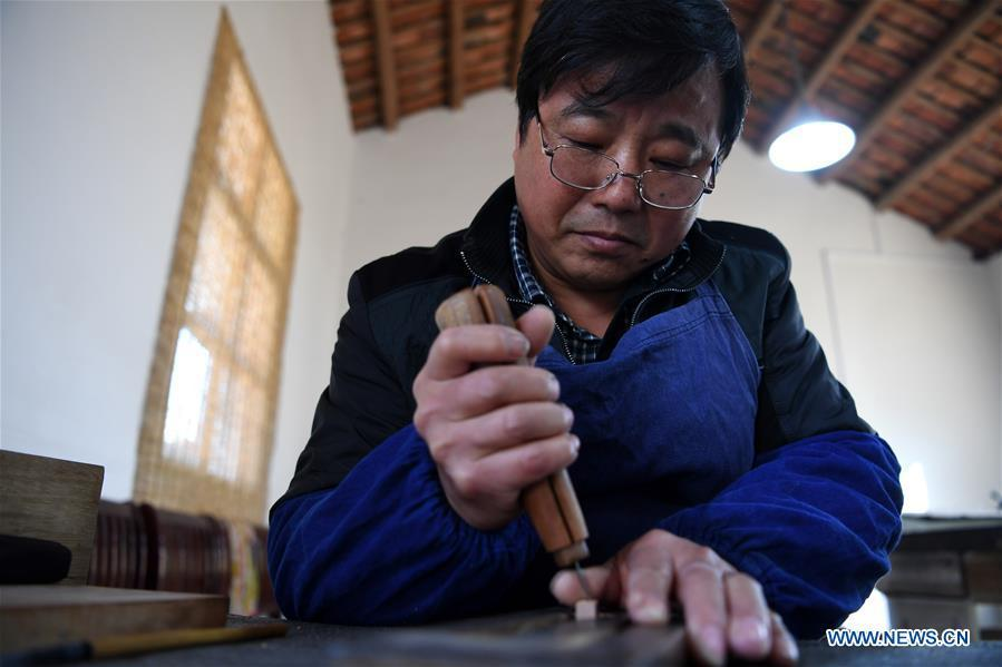 Lei Shitai works in Chanshan Village of Qinxi Town, Jingxian County, in east China\'s Anhui Province, Nov. 23, 2018. Lei, 52, born in neighboring Jiangxi Province, started his career as a typography printer when he finished his apprenticeship with his uncle who he followed since he was 17. The traditional printing method witnessed an increasingly hard time in the recent years as a livelihood. It was in 2017 when he decided to move to Chanshan at the invitation of Kai Yuanhong, a local cabinet maker, to cooperate in a broader way. Lei is now working with the traditional technique in a larger scale. (Xinhua/Liu Junxi)