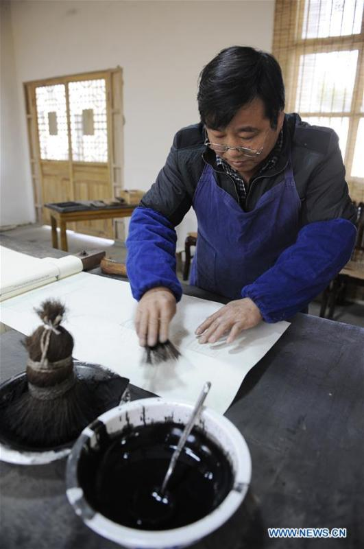 Lei Shitai works on a paper as he prints a book in Chanshan Village of Qinxi Town, Jingxian County, in east China\'s Anhui Province, Nov. 23, 2018. Lei, 52, born in neighboring Jiangxi Province, started his career as a typography printer when he finished his apprenticeship with his uncle who he followed since he was 17. The traditional printing method witnessed an increasingly hard time in the recent years as a livelihood. It was in 2017 when he decided to move to Chanshan at the invitation of Kai Yuanhong, a local cabinet maker, to cooperate in a broader way. Lei is now working with the traditional technique in a larger scale. (Xinhua/Xu Liang)