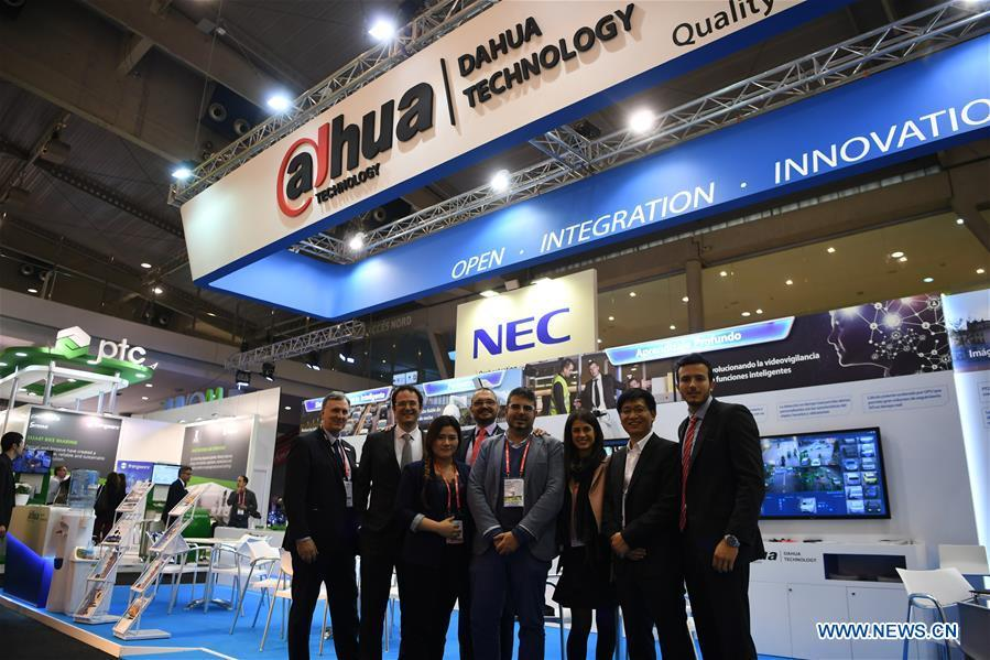 Staff members of Zhejiang Dahua Technology Co. Ltd. pose for a group photo during the Smart City Expo World Congress in Barcelona, Spain, on Nov. 15, 2017. More and more Spanish consumers accept Chinese high-tech brands, which now can be seen in daily life across Spain.(Xinhua/Guo Qiuda)