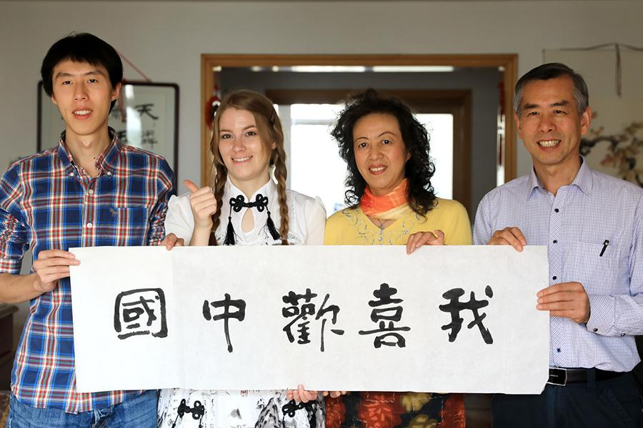 Emily Francis and her family hold her calligraphy work at home in Shijiazhuang on Nov. 24, 2018. (Photo/Xinhua)
