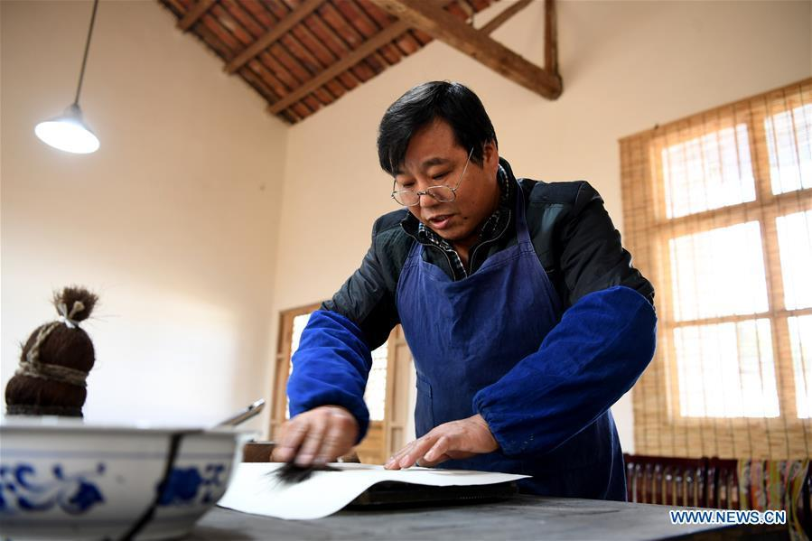 Lei Shitai works on a paper as he prints a book in Chanshan Village of Qinxi Town, Jingxian County, in east China\'s Anhui Province, Nov. 23, 2018. Lei, 52, born in neighboring Jiangxi Province, started his career as a typography printer when he finished his apprenticeship with his uncle who he followed since he was 17. The traditional printing method witnessed an increasingly hard time in the recent years as a livelihood. It was in 2017 when he decided to move to Chanshan at the invitation of Kai Yuanhong, a local cabinet maker, to cooperate in a broader way. Lei is now working with the traditional technique in a larger scale. (Xinhua/Zhang Duan)