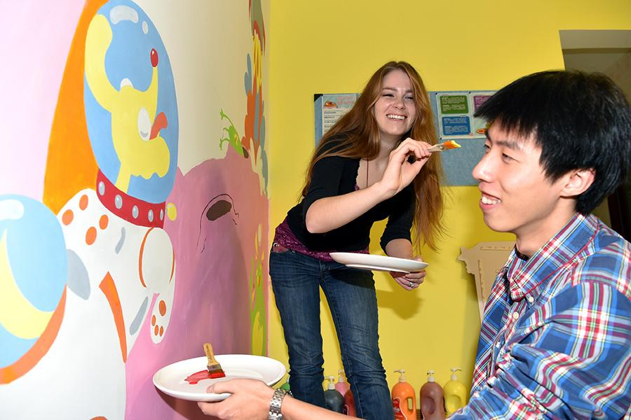 Francis and her husband paint a wall at their education studio in Shijiazhuang on Nov. 24, 2018.  (Photo/Xinhua)