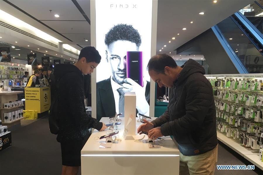 People select OPPO smart phones in a shopping mall in Barcelona, Spain, on Nov. 25, 2018. More and more Spanish consumers accept Chinese high-tech brands, which now can be seen in daily life across Spain. (Xinhua/Zheng Huansong)