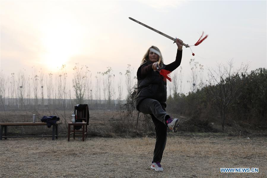 Ana Fidalgo practices Taiji swords in Chenjiagou Village of Wenxian County, central China\'s Henan Province, Nov. 25, 2018. Ana, who comes from Sao Paulo, Brazil, loves Chinese culture, and is a fan of Taiji. It\'s the third time that she comes to Chenjiagou Village to study Taiji. She has taught what she has learned in China in her hometown when coming back to Brazil in recent years, hoping to benefit more people. (Xinhua/Xu Hongxing)