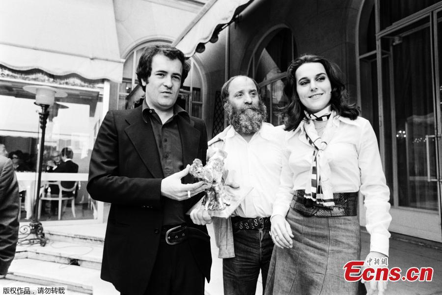 Italian Bernardo Bertolucci flanked by French sculptor Cesar and its millionth spectator , poses after being awarded the \