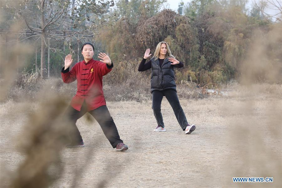 Ana Fidalgo (R) practices Taiji under the guidance of coach Chen Huili in Chenjiagou Village of Wenxian County, central China\'s Henan Province, Nov. 25, 2018. Ana, who comes from Sao Paulo, Brazil, loves Chinese culture, and is a fan of Taiji. It\'s the third time that she comes to Chenjiagou Village to study Taiji. She has taught what she has learned in China in her hometown when coming back to Brazil in recent years, hoping to benefit more people. (Xinhua/Xu Hongxing)
