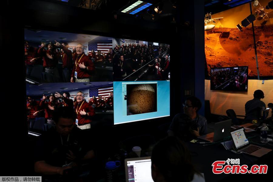 The mission control team at NASA\'s Jet Propulsion Laboratory (JPL) react on a video screen as the spaceship Insight, NASA\'s first robotic lander dedicated to studying the deep interior of Mars, sends its first picture back to JPL, in Pasadena, California, U.S. November 26, 2018.(Photo/Agencies)