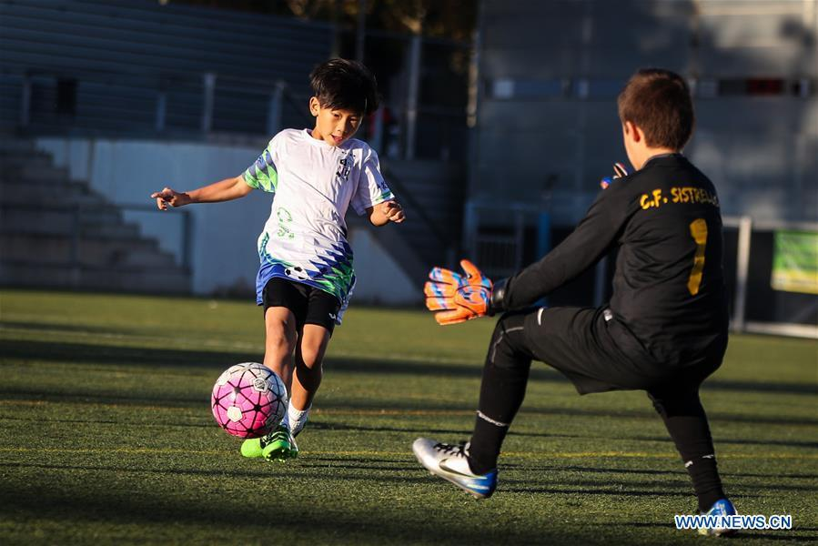 Xu Tianze (L) drives the ball during a match against Club Sistrells in Badalona, Province of Barcelona, Spain, Nov. 24, 2018. Spain has a mature football industry which attracts many young Chinese football lovers. The Sport CSKH, founded by an overseas Chinese in Barcelona, has been a bridge linking Chinese young football players with Spanish football culture. (Xinhua/Zheng Huansong)