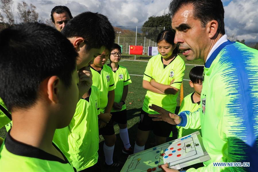 Coach Miguel Duran (R) instructs Chinese young football players at the Sport CSHK training ground in Sant Esteve de Palautordera, Province of Barcelona, Spain, Nov. 24, 2018. Spain has a mature football industry which attracts many young Chinese football lovers. The Sport CSKH, founded by an overseas Chinese in Barcelona, has been a bridge linking Chinese young football players with Spanish football culture. (Xinhua/Zheng Huansong)
