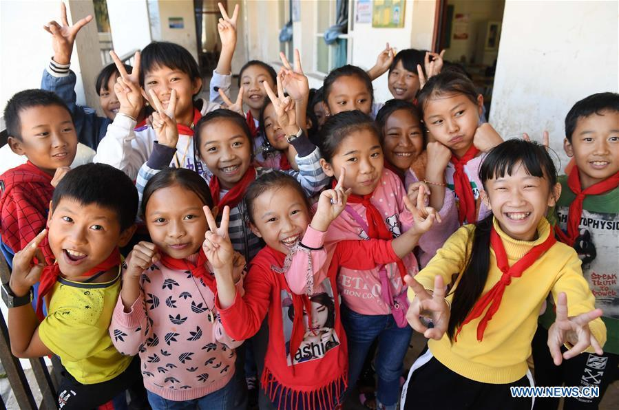 Students pose for photos at the Ethnic Primary School in Jino Ethnic Township on Jino Mountain in Jinghong of Xishuangbanna Dai Autonomous Prefecture, southwest China\'s Yunnan Province, Nov. 20, 2018. Most of the 712 students enrolled at the school are of the Jino ethnic descent. With a population of slightly over 20,000, the Jino people had only been officially acknowledged in 1979 as an independent ethnic group of China. Until 1949, most of them had lived for generations in primitive mountain tribes in southwest China\'s Yunnan Province. Over the four decades since it embraced the reform and opening-up policy, China has spared no effort to support ethnic groups with smaller populations. Life on Jino Mountain, where most Jino communities are located, saw positive changes in parallel with improvements in local politics, economy, technology, education, culture, health care, ecology, ethnic development and other social undertakings. Just like its 55 ethnic brethren, the Jino people also benefit from China\'s reform and opening-up in seeking a prosperous life. In Jino Ethnic Township on the Jino Mountain, residents now have direct access to road, water, electricity, TV and radio, as well as the mobile network. Ninety percent of the residents have moved into new houses. Most residents own motorcycles and tractors, and some of them have purchased cars. More people have increased their income by selling local specialty products via the internet, whereas in the past, doing business was perceived as a shame. Currently, the primary education in Jino Ethnic Township achieved 100 percent coverage for all school-age children. More than 99 percent of residents have joined the rural cooperative medical insurance programme. The Jino ethnic culture undergoes protection and inheritance: the great drum dance of the Jino people has been listed as one of China\'s national intangible cultural heritages. (Xinhua/Lin Yiguang)