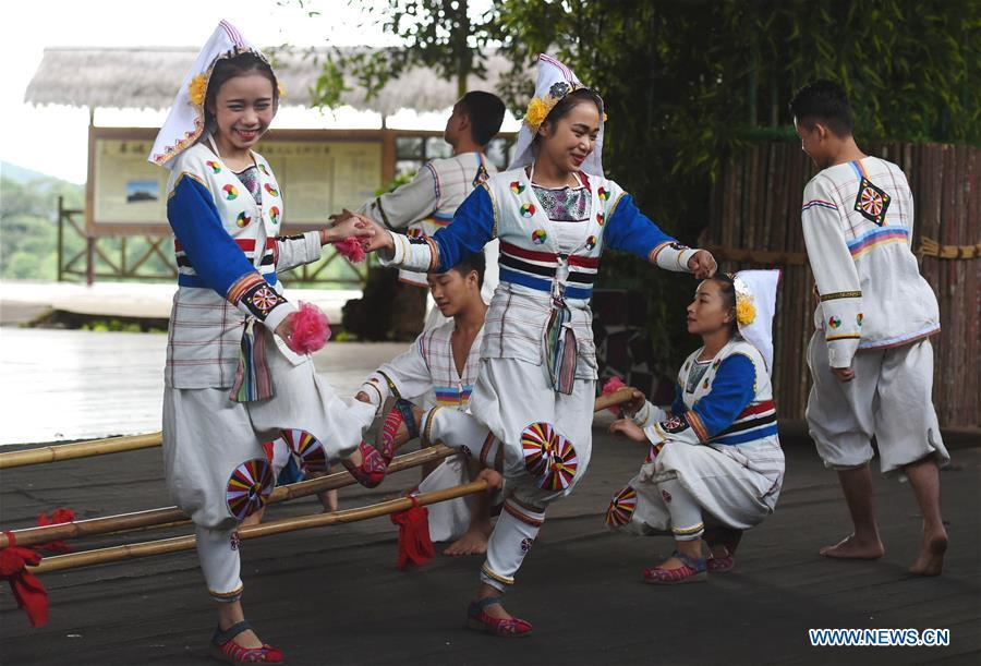 Jino youths perform a folk dance for tourists in Bapo Village of Jino Ethnic Township on Jino Mountain, Jinghong, in Xishuangbanna Dai Autonomous Prefecture, southwest China\'s Yunnan Province, Nov. 5, 2015. With a population of slightly over 20,000, the Jino people had only been officially acknowledged in 1979 as an independent ethnic group of China. Until 1949, most of them had lived for generations in primitive mountain tribes in southwest China\'s Yunnan Province. Over the four decades since it embraced the reform and opening-up policy, China has spared no effort to support ethnic groups with smaller populations. Life on Jino Mountain, where most Jino communities are located, saw positive changes in parallel with improvements in local politics, economy, technology, education, culture, health care, ecology, ethnic development and other social undertakings. Just like its 55 ethnic brethren, the Jino people also benefit from China\'s reform and opening-up in seeking a prosperous life. In Jino Ethnic Township on the Jino Mountain, residents now have direct access to road, water, electricity, TV and radio, as well as the mobile network. Ninety percent of the residents have moved into new houses. Most residents own motorcycles and tractors, and some of them have purchased cars. More people have increased their income by selling local specialty products via the internet, whereas in the past, doing business was perceived as a shame. Currently, the primary education in Jino Ethnic Township achieved 100 percent coverage for all school-age children. More than 99 percent of residents have joined the rural cooperative medical insurance programme. The Jino ethnic culture undergoes protection and inheritance: the great drum dance of the Jino people has been listed as one of China\'s national intangible cultural heritages. (Xinhua/Lin Yiguang)