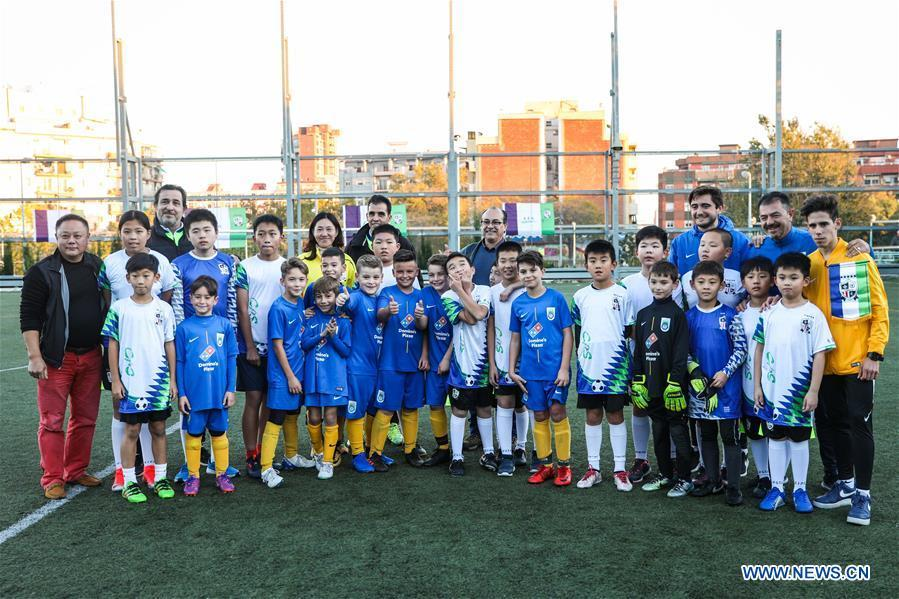 Chinese young football players pose for photos with members of Club Sistrells after their match in Badalona, Province of Barcelona, Spain, Nov. 24, 2018. Spain has a mature football industry which attracts many young Chinese football lovers. The Sport CSKH, founded by an overseas Chinese in Barcelona, has been a bridge linking Chinese young football players with Spanish football culture. (Xinhua/Zheng Huansong)
