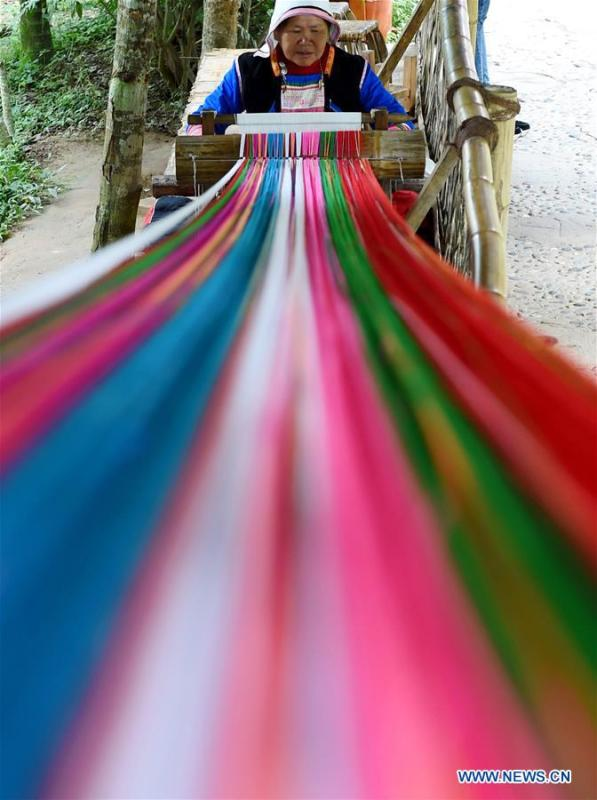 A Jino woman weaves cloths using a traditional hand loom in Bapo Village of Jinuo Ethnic Township on Jino Mountain in Jinghong of Xishuangbanna Dai Autonomous Prefecture, southwest China\'s Yunnan Province, Nov. 5, 2015. With a population of slightly over 20,000, the Jino people had only been officially acknowledged in 1979 as an independent ethnic group of China. Until 1949, most of them had lived for generations in primitive mountain tribes in southwest China\'s Yunnan Province. Over the four decades since it embraced the reform and opening-up policy, China has spared no effort to support ethnic groups with smaller populations. Life on Jino Mountain, where most Jino communities are located, saw positive changes in parallel with improvements in local politics, economy, technology, education, culture, health care, ecology, ethnic development and other social undertakings. Just like its 55 ethnic brethren, the Jino people also benefit from China\'s reform and opening-up in seeking a prosperous life. In Jino Ethnic Township on the Jino Mountain, residents now have direct access to road, water, electricity, TV and radio, as well as the mobile network. Ninety percent of the residents have moved into new houses. Most residents own motorcycles and tractors, and some of them have purchased cars. More people have increased their income by selling local specialty products via the internet, whereas in the past, doing business was perceived as a shame. Currently, the primary education in Jino Ethnic Township achieved 100 percent coverage for all school-age children. More than 99 percent of residents have joined the rural cooperative medical insurance programme. The Jino ethnic culture undergoes protection and inheritance: the great drum dance of the Jino people has been listed as one of China\'s national intangible cultural heritages. (Xinhua/Lin Yiguang)