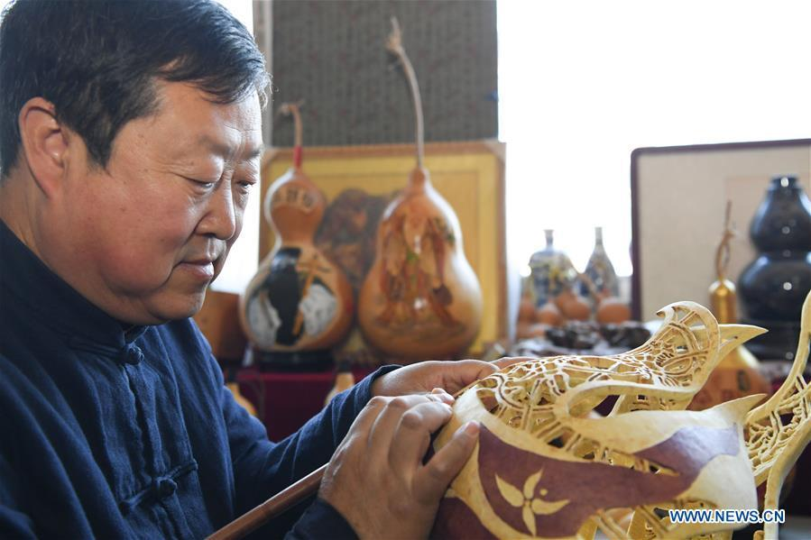 Wang Guowei carves gourd handicraft at his studio in Tieling, northeast China\'s Liaoning Province, Nov. 26, 2018. Wang Guowei who is adept in painting was awarded provincial-level handicraft master title for producing exquisite gourd handicrafts with vivid images. (Xinhua/Long Lei)
