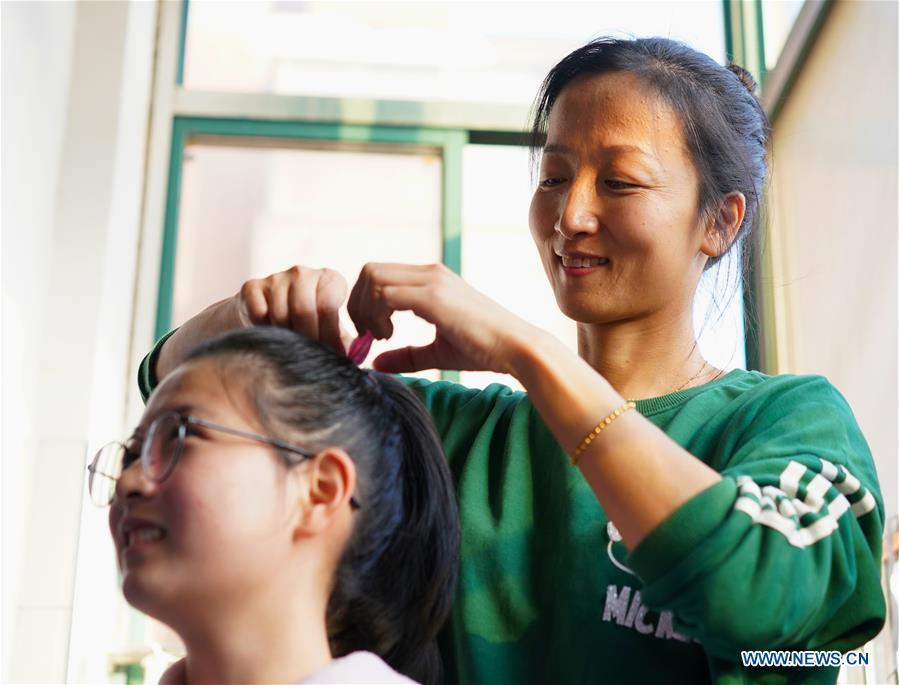 Teacher Zeng Wenping (R) combs a student\'s hair at Qiyin school in Nanchang, capital of east China\'s Jiangxi Province, Nov. 26, 2018. Zeng, 43, has been engaged in special education for 21 years ever since she graduated from university. Hearing impaired students enjoy the all-encompassing heartfelt and intensive care by Zeng and consider her as more than a teacher but a sister. (Xinhua/Hu Chenhuan)