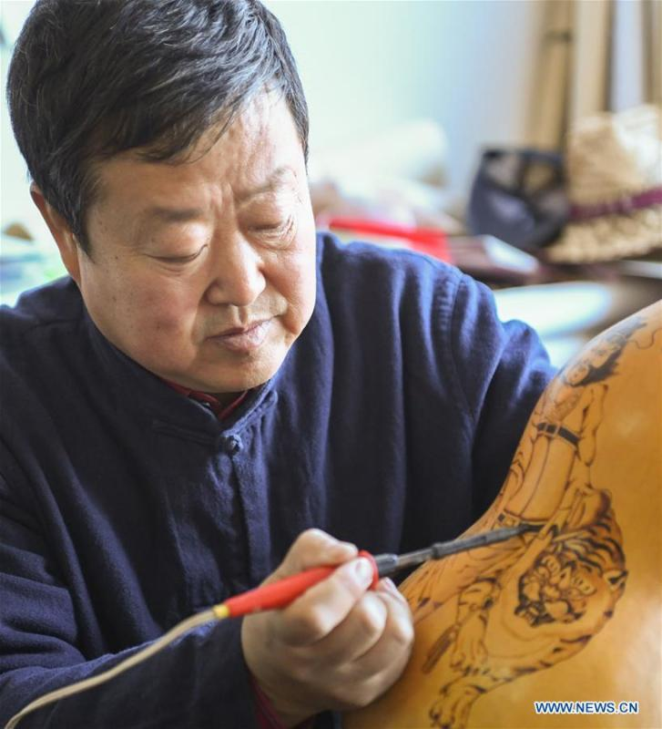 Wang Guowei makes gourd handicraft at his studio in Tieling, northeast China\'s Liaoning Province, Nov. 26, 2018. Wang Guowei who is adept in painting was awarded provincial-level handicraft master title for producing exquisite gourd handicrafts with vivid images. (Xinhua/Long Lei)
