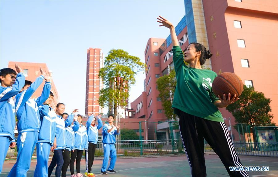 Teacher Zeng Wenping (R) plays basketball with students at Qiyin school in Nanchang, capital of east China\'s Jiangxi Province, Nov. 26, 2018. Zeng, 43, has been engaged in special education for 21 years ever since she graduated from university. Hearing impaired students enjoy the all-encompassing heartfelt and intensive care by Zeng and consider her as more than a teacher but a sister. (Xinhua/Hu Chenhuan)