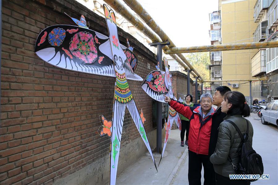 Fu Xianming (1st L, front) introduces self-made kites to neighbors in Shijiazhuang, capital of north China\'s Hebei Province, Nov. 21, 2018. Fu Xianming, a 66-year-old craftsman, has devoted himself in kites making for 20 years. Fu and his wife have made more than 1,500 kites of various shapes since 1998. (Xinhua/Zhang Haiqiang)