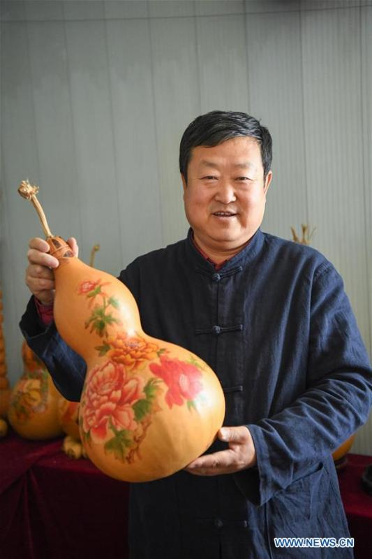 Wang Guowei displays gourd handicraft at his studio in Tieling, northeast China\'s Liaoning Province, Nov. 26, 2018. Wang Guowei who is adept in painting was awarded provincial-level handicraft master title for producing exquisite gourd handicrafts with vivid images. (Xinhua/Long Lei)