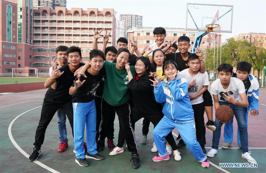 Teacher Zeng Wenping (in green shirt) poses for a photo with her students at Qiyin school in Nanchang, capital of east China\'s Jiangxi Province, Nov. 26, 2018. Zeng, 43, has been engaged in special education for 21 years ever since she graduated from university. Hearing impaired students enjoy the all-encompassing heartfelt and intensive care by Zeng and consider her as more than a teacher but a sister. (Xinhua/Hu Chenhuan)